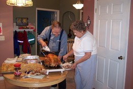 Dad and Aunt Lois carving the beast