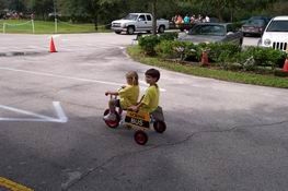 Catching a ride in the Trike-A-Thon with his classmate